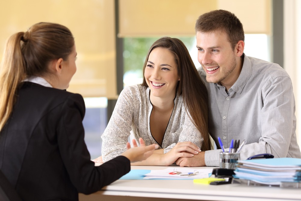 Happy,Couple,Talking,With,A,Real,Estate,Agent,At,Office
